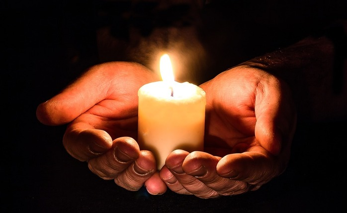 2 hands holding a candle