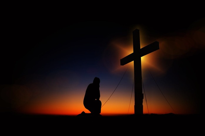 person kneeling at the cross
