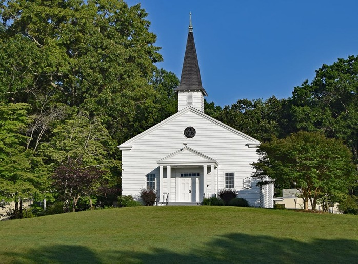 white church building surrounded by grass and trees