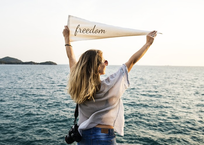 woman holding up freedom sign in front of water