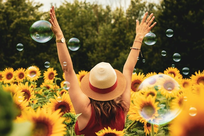 woman playing with bubbles in the midst of sunflowers