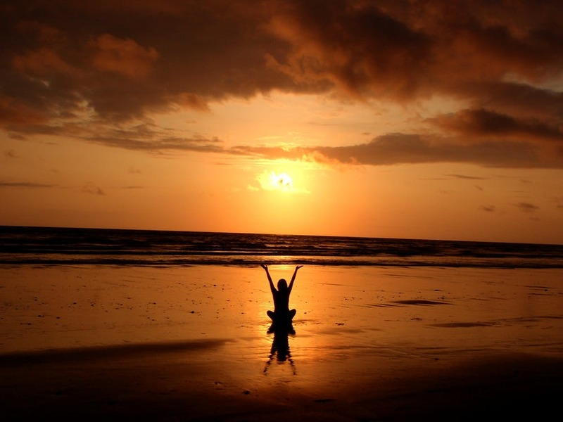 woman sitting on beach with hands lifted  - God Restores My Soul
